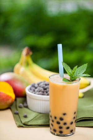 pearl tea: Mango smoothie bubble tea with fruit and tapioca pearls in the garden