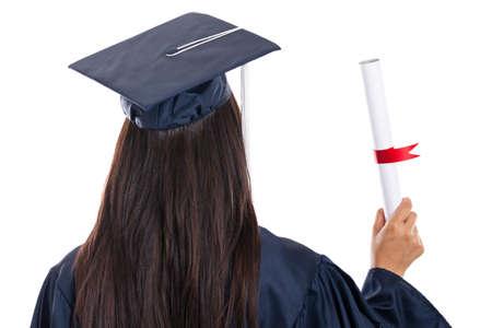 toga y birrete: Vista posterior de la universidad graduado holding diploma aislados en blanco