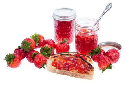 Jars of jam with strawberries and toast isolated on a white background photo