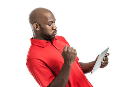 Handsome African American man in his late 20s pumping fist excited playing on a tablet PC isolated on a white background photo