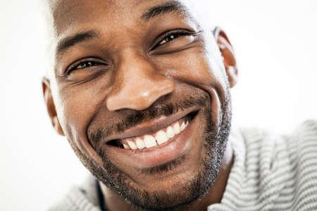 흰색 배경에 고립 된 그의 20 대에 행복 흑인 남자의 초상화를 닫습니다