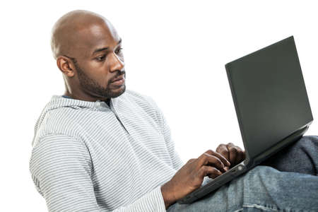 late 20s: Handsome late 20s black man typing on the computer isolated on a white background Stock Photo