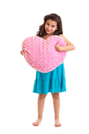 7 year old girl: Cute 7 year old girl holding a Valentine s heart pillow isolated on white Stock Photo
