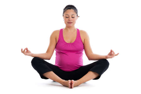dhyana: Beautiful fit Hispanic pregnant woman sitting on the floor in cobbler s pose meditating isolated on a white background