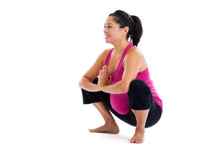 squatting: Mujer embarazada hisp�nica hermosa del ajuste en cuclillas plantean aislados en un fondo blanco