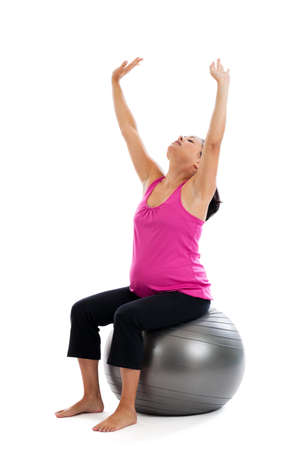 ball stretching: Beautiful fit Hispanic pregnant woman sitting on an exercise ball stretching with arms extended isolated on a white background Stock Photo