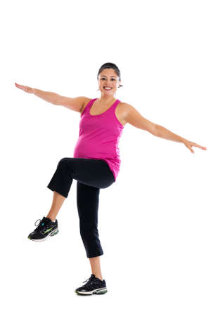 Beautiful fit Hispanic pregnant woman doing low impact aerobic knee raises with arms extended  isolated on a white background