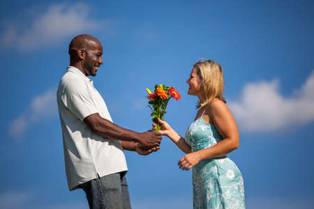 biracial: Handsome black man giving beautiful caucasian woman flowers on a sunny summer afternoon