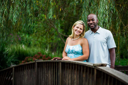 Beautiful interracial couple portrait at a park in summer standing on a bridge photo