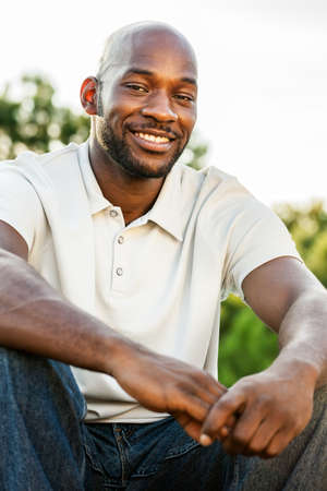 late 20s: Portrait of a handsome black man in his late 20s sitting at the park outdoors in summer