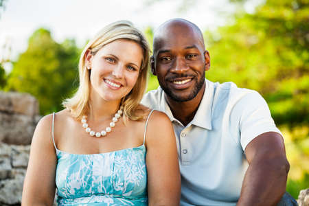 Portrait of a mixed race couple sitting at the park in summer photo