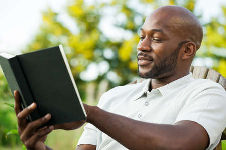Handsome African American man in his late 20s reading a book at the park on a summer day photo