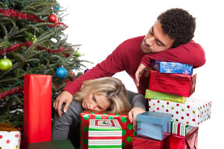 tired man: Exhausted Christmas couple slumped over presents