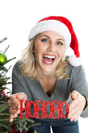 wearing santa hat: Woman wearing Santa hat holding Christmas ornament