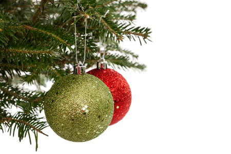Red and green Christmas ornaments dangling from evergreen tree branches isolated on white