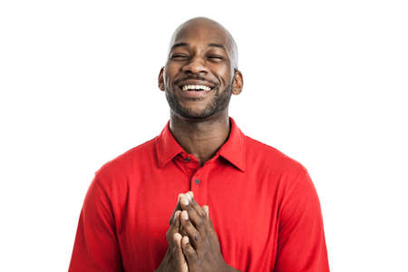 Handsome late 20s black man praying with hopeful expression isolated on a white background Standard-Bild