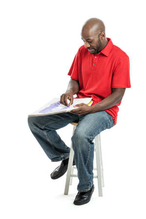 Handsome late 20s black man artist drawing a picture with pastels on a sketch pad isolated on white photo