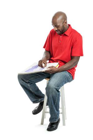 Knappe late 20s zwarte man kunstenaar tekenen van een beeld met pastelkleuren op een schetsblok op wit wordt geïsoleerd