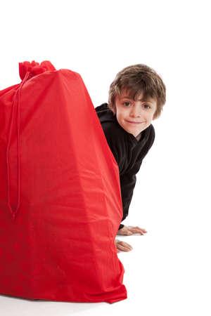 santa s bag: 8 year old boy hiding behind Santa s Christmas sack