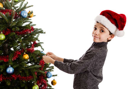 9 year old: 9 year old boy wearing a Santa hat decorating a Christmas tree isolated on white background