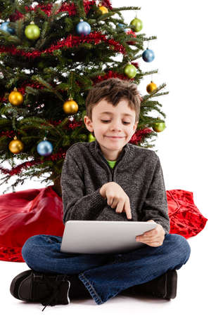 9 year old boy touching a tablet pc in front of a Christmas tree isolated on white background photo