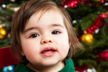Beautiful 1 year old girl in front of the Christmas tree photo