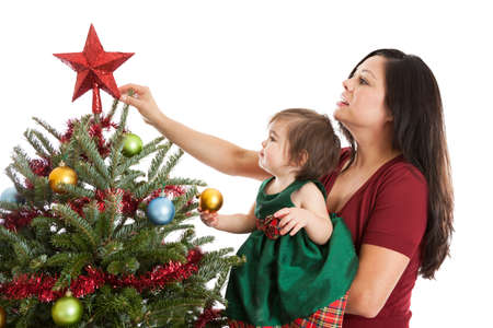 Mother and baby daughter putting the star on top of a Christmas tree photo