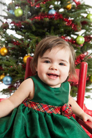 Adorable 1 year old girl sitting in front of the Christmas tree photo