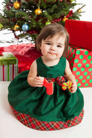1 year old: 1 year old girl eating cookies in front of the Christmas tree