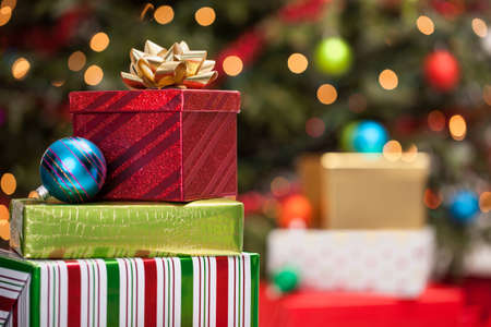 Christmas gift boxes with bow in front of a tree with defocused lights