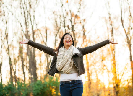 late 20s: Young Asian carefree woman in mid 20s with arms in the air at the park on an autumn late afternoon Stock Photo