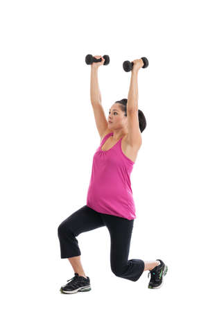 Beautiful Hispanic pregnant woman doing lunges with light weights photo