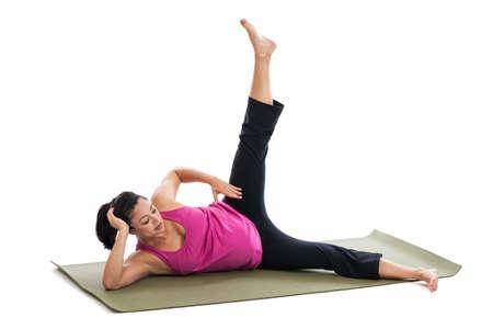 raises: Beautiful Hispanic pregnant woman doing leg extension on yoga mat Stock Photo