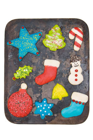 Homemade iced Christmas sugar cookies on baking stone isolated on white photo