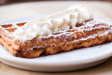 Belgian waffle with whipped cream and powdered sugar on top