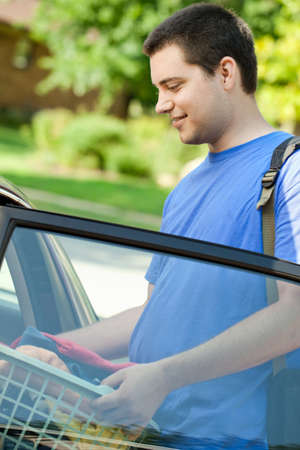 open car door: College student putting laundry in car going back to school  Stock Photo