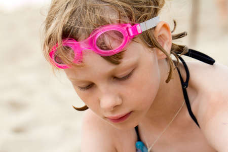 Sad girl in swimming goggles at the beach photo