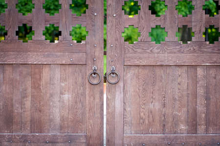 Ancient closed wooden gate with two door knocker rings photo