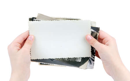 Human hands holding batch of the vintage photos isolated on white background photo