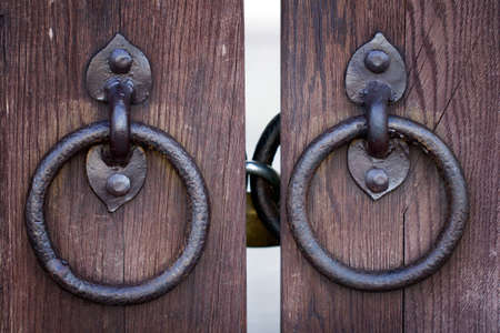 Ancient wooden gate with two door knocker rings close-up shot photo