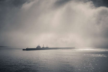 fog on the sea entering the port, covering a merchant ship Imagens