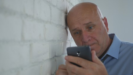 Upset Businessman Looking Disappointed on Cell Phone Text Stock Photo