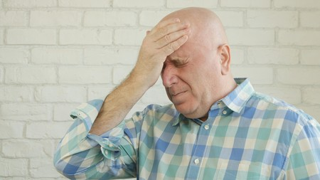 Man Suffering a Big and Painful Headache with White Brick Wall in Background