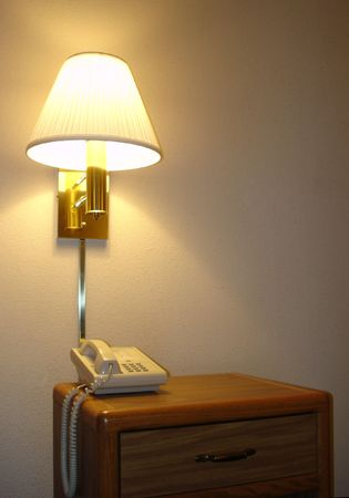 Standard set in most Hotels - Bedside Stand with a Drawer, Phone, Wall Mounted Lamp Stok Fotoğraf