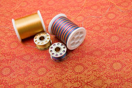 Closeup of spools with thread on fabric photo