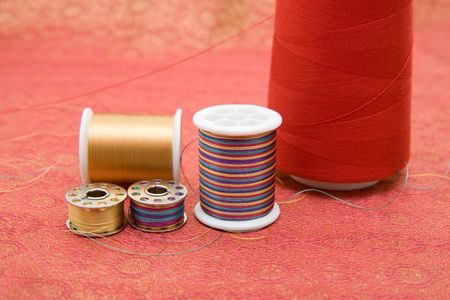 Closeup of spools and bobbin with thread on fabric 写真素材