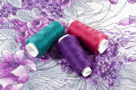 패턴으로 헝겊 조각에 녹색, 분홍색과 보라색 스레드의 세 bobbins 스톡 콘텐츠