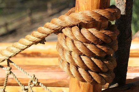 Tight rope knot on wood of ship; close up photo
