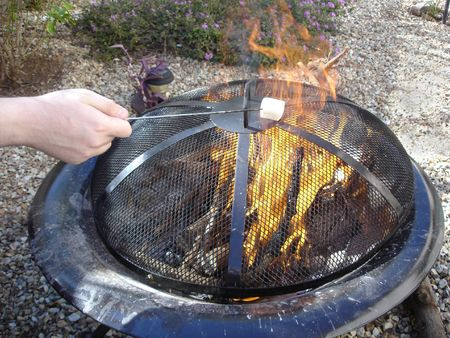 fire pit: Roasting Sweet White Marshmallow above Flaming Fire Pit