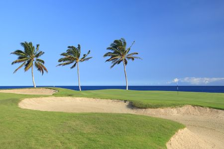 Green Golf Course with Sand Traps on Ocean Shore of Kona Island, HI Stock Photo